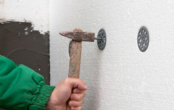 За допомогою перфоратора і молотка закріплюємо за п`ять дюбелів на кожен лист утеплювача