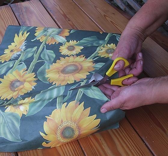 Акуратно виріжте з листа паперу для декупажу зображення соняшників.